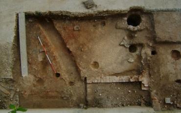 Obsérvense las huellas de poste, el pozo y la cisterna de ladrillos que se encuentra adosada a la pared noroeste del edificio