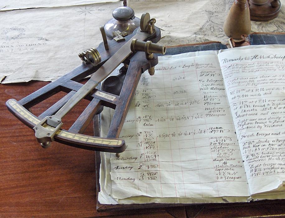Octante junto a cuaderno de bitácora